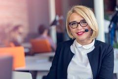 Усмехаясь женщина агента с шлемофонами Портрет работника центра телефонного обслуживания на офисе Стоковое Изображение