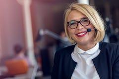 Усмехаясь женщина агента с шлемофонами Портрет работника центра телефонного обслуживания на офисе Стоковое Изображение RF