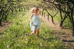 Усмехаясь женщина бежать среди цветков Стоковое Изображение RF