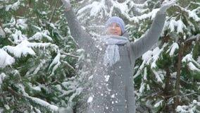 Усмехаясь женщина бросает снег в воздухе в сосновом лесе на зимний день в замедленном движении акции видеоматериалы