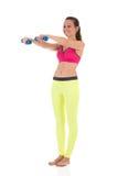 Усмехаясь женщина брюнет в гетры спорт неоновых желтых и розовом бюстгальтере делая сложные тренировки для мышц рук используя ган Стоковое Изображение RF