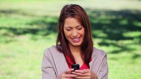 Усмехаясь женщина брюнет отправляя СМС на ее мобильном телефоне сток-видео