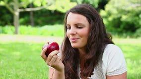 Усмехаясь женщина брюнет с волосами есть красное яблоко видеоматериал