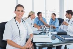 Усмехаясь женщина врачует смотреть камеру перед ее командой стоковое изображение rf
