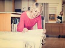 Усмехаясь женщина выбирая интересную ткань Стоковое Изображение