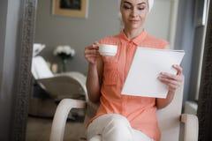Усмехаясь женщина выпивает кофе после мыть голову в салоне стоковое изображение