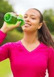 Усмехаясь женщина выпивая от бутылки Стоковые Изображения