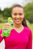 Усмехаясь женщина выпивая от бутылки Стоковое Изображение