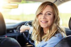 Усмехаясь женщина в автомобиле смотрит назад на летний день стоковые фото