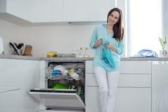 Усмехаясь женщина в белых джинсах и рубашке бирюзы с чашкой и полотенцем в ее руках, стоя рядом с открытой судомойкой в w стоковая фотография rf