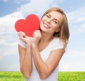 Усмехаясь женщина в белой футболке держа красное сердце стоковые фотографии rf