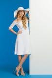 Усмехаясь женщина в белых платье и шляпе лета представляет близко к знамени Стоковое Фото