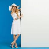 Усмехаясь женщина в белых платье и шляпе лета стоит близко к знамени и указывает на ее Стоковая Фотография