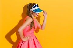 Усмехаясь женщина в голубом забрале Солнця на желтой предпосылке Стоковое Изображение RF