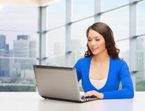 Усмехаясь женщина в голубых одеждах с портативным компьютером Стоковые Фотографии RF