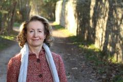 Усмехаясь женщина в ее 60s outdoors стоковые изображения
