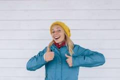 Усмехаясь женщина в желтом цвете связала шляпу и синий пиджак показывая большие пальцы руки вверх люди принципиальной схемы счаст Стоковая Фотография