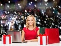 Усмехаясь женщина в красной рубашке с подарками и компьтер-книжкой Стоковое Фото