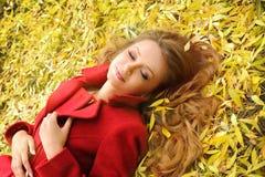 Усмехаясь женщина в красном пальто лежа в листьях осени в парке Стоковая Фотография