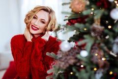 Усмехаясь женщина в красном свитере над предпосылкой рождественской елки стоковая фотография