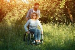 Усмехаясь женщина в кресло-коляске с супругом в парке на солнечный день стоковая фотография rf