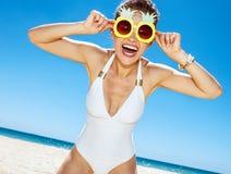 Усмехаясь женщина в купальнике и в стиле фанк стеклах ананаса на пляже Стоковые Фото