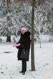 Усмехаясь женщина в меховой шыбе остается около дерева в парке стоковая фотография