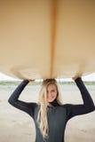 Усмехаясь женщина в мокрой одежде держа surfboard надземный на пляже Стоковые Изображения