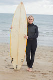 Усмехаясь женщина в мокрой одежде держа surfboard на пляже Стоковые Изображения