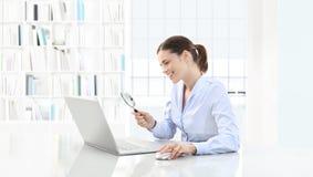 Усмехаясь женщина в офисе ищет на компьютере с лупой стоковая фотография