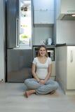 Усмехаясь женщина в пижамах сидя на поле на кухне рядом с ope Стоковое Изображение RF