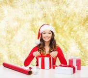 Усмехаясь женщина в подарках упаковки шляпы хелпера santa Стоковое Фото