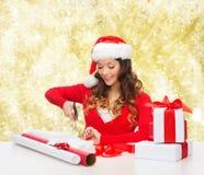 Усмехаясь женщина в подарочной коробке упаковки шляпы хелпера santa Стоковая Фотография RF