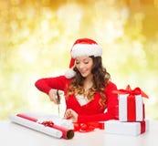 Усмехаясь женщина в подарочной коробке упаковки шляпы хелпера santa Стоковые Фотографии RF