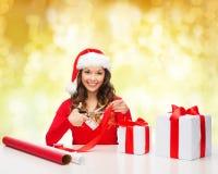 Усмехаясь женщина в подарочной коробке упаковки шляпы хелпера santa Стоковые Изображения