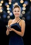 Усмехаясь женщина в платье вечера с smartphone Стоковое Изображение RF
