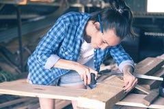 Усмехаясь женщина в рулетке домашней мастерской измеряя деревянная доска перед пилить, плотничество стоковые фотографии rf