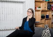 Усмехаясь женщина в стеклах имея телефонный разговор клетки через мобильный телефон пока отдыхающ в доме стоковые фото