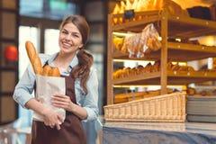 Усмехаясь женщина в хлебопекарне стоковое изображение rf