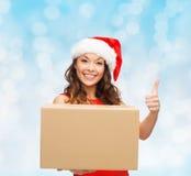 Усмехаясь женщина в шляпе хелпера santa с коробкой пакета Стоковое фото RF