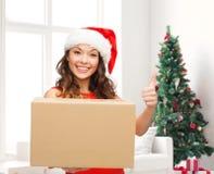 Усмехаясь женщина в шляпе хелпера santa с коробкой пакета Стоковые Фотографии RF
