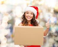 Усмехаясь женщина в шляпе хелпера santa с коробкой пакета Стоковое Изображение RF