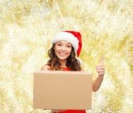 Усмехаясь женщина в шляпе хелпера santa с коробкой пакета Стоковое Фото
