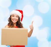 Усмехаясь женщина в шляпе хелпера santa с коробкой пакета Стоковая Фотография RF