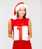 Усмехаясь женщина в шляпе хелпера santa с коробкой подарка стоковые изображения rf