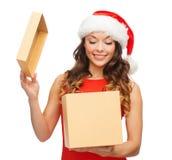 Усмехаясь женщина в шляпе хелпера santa с коробкой подарка Стоковое фото RF