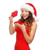 Усмехаясь женщина в шляпе хелпера santa с подарочной коробкой стоковое фото rf