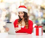 Усмехаясь женщина в шляпе santa с ПК подарка и таблетки Стоковое Изображение