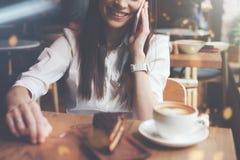 Усмехаясь женщина говоря на телефоне в кафе Вкусные шоколадный торт и кофе на таблице Яркое солнечное утро в кафе Стоковое фото RF