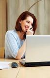 Усмехаясь женщина говоря на телефоне на ее рабочем месте Стоковые Фотографии RF